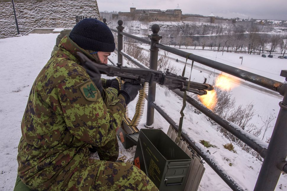 An Estonian paramilitary volunteer fires a machine gun yards from the border with Russia. Jan. 14.