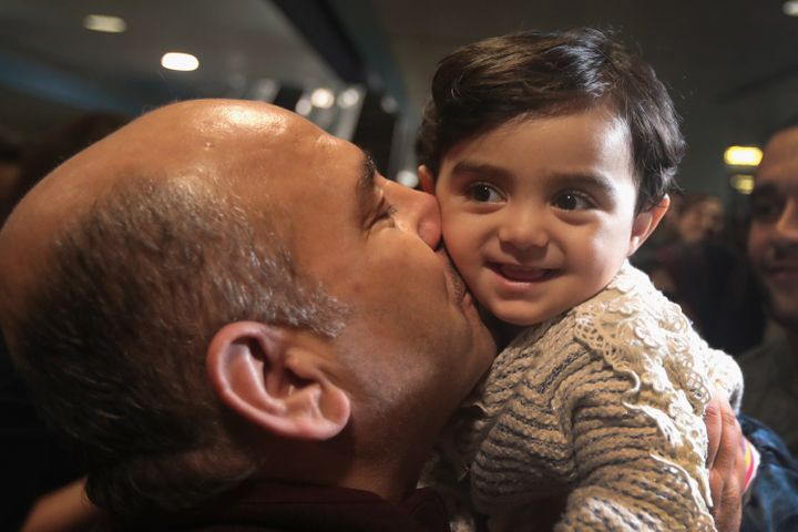 Khaled Haj Khalaf kisses his grandaughter Shams after she arrived with her mother and father at O'Hare Airport on a flight fr