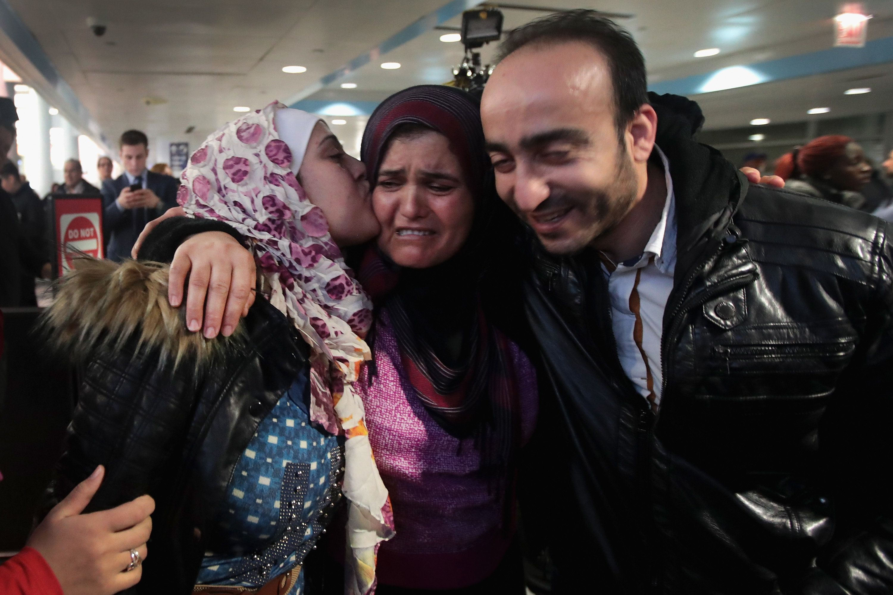 Syrian refugee Baraa Hajj Khalaf, left, and her husband, Abulmajeed, are greeted by her mother, Fattuom, after a second-attem