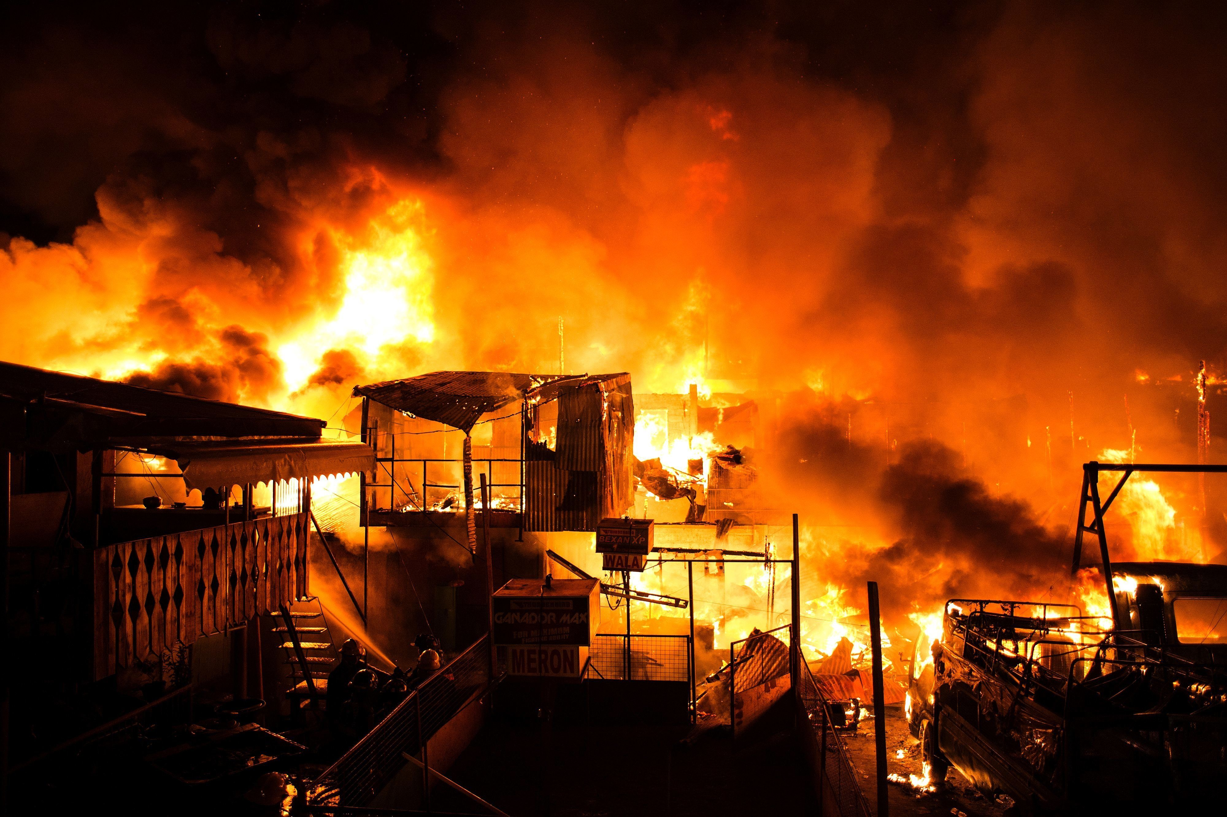 CORRECTION - A fire burns through an informal settlers community as it burns hundreds of houses in Delpan, Tondo, Manila on February 7, 2017. / AFP / NOEL CELIS / The erroneous mention[s] appearing in the metadata of this photo by NOEL CELIS has been modified in AFP systems in the following manner: [February] instead of [January]. Please immediately remove the erroneous mention[s] from all your online services and delete it (them) from your servers. If you have been authorized by AFP to distribute it (them) to third parties, please ensure that the same actions are carried out by them. Failure to promptly comply with these instructions will entail liability on your part for any continued or post notification usage. Therefore we thank you very much for all your attention and prompt action. We are sorry for the inconvenience this notification may cause and remain at your disposal for any further information you may require.        (Photo credit should read NOEL CELIS/AFP/Getty Images)