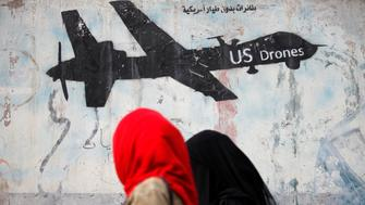 Women walk past a graffiti, denouncing strikes by U.S. drones in Yemen, painted on a wall in Sanaa, Yemen February 6, 2017. Picture taken February 6, 2017.  REUTERS/Khaled Abdullah