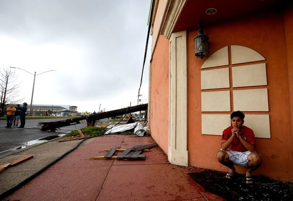 A man sits next to the side of a building after a tornado touched down along Chef MenteurAvenue.