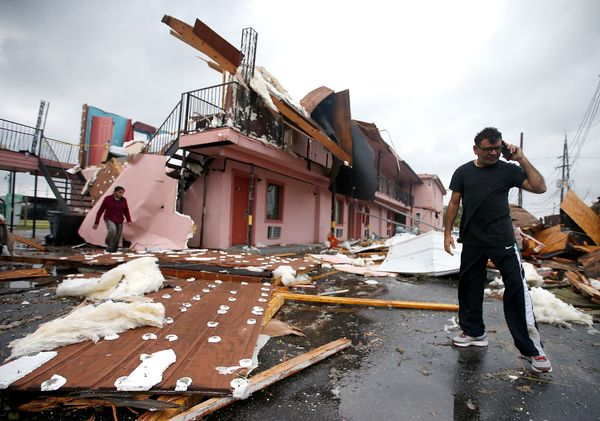 A man walks through the debris of what was once a motel on Chef Menteur Avenue after a tornado touched down Tuesday in N