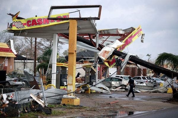 A police officer walks through a damaged gas station along Chef Menteur Avenue.