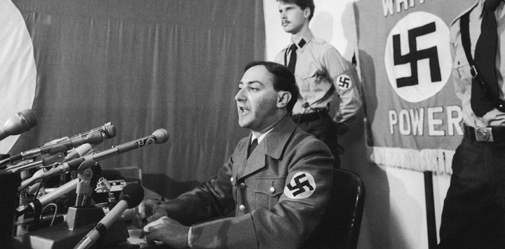 American Nazi leader Frank Collin, flanked by members of the National Socialist Party of America, speaksat a news confe
