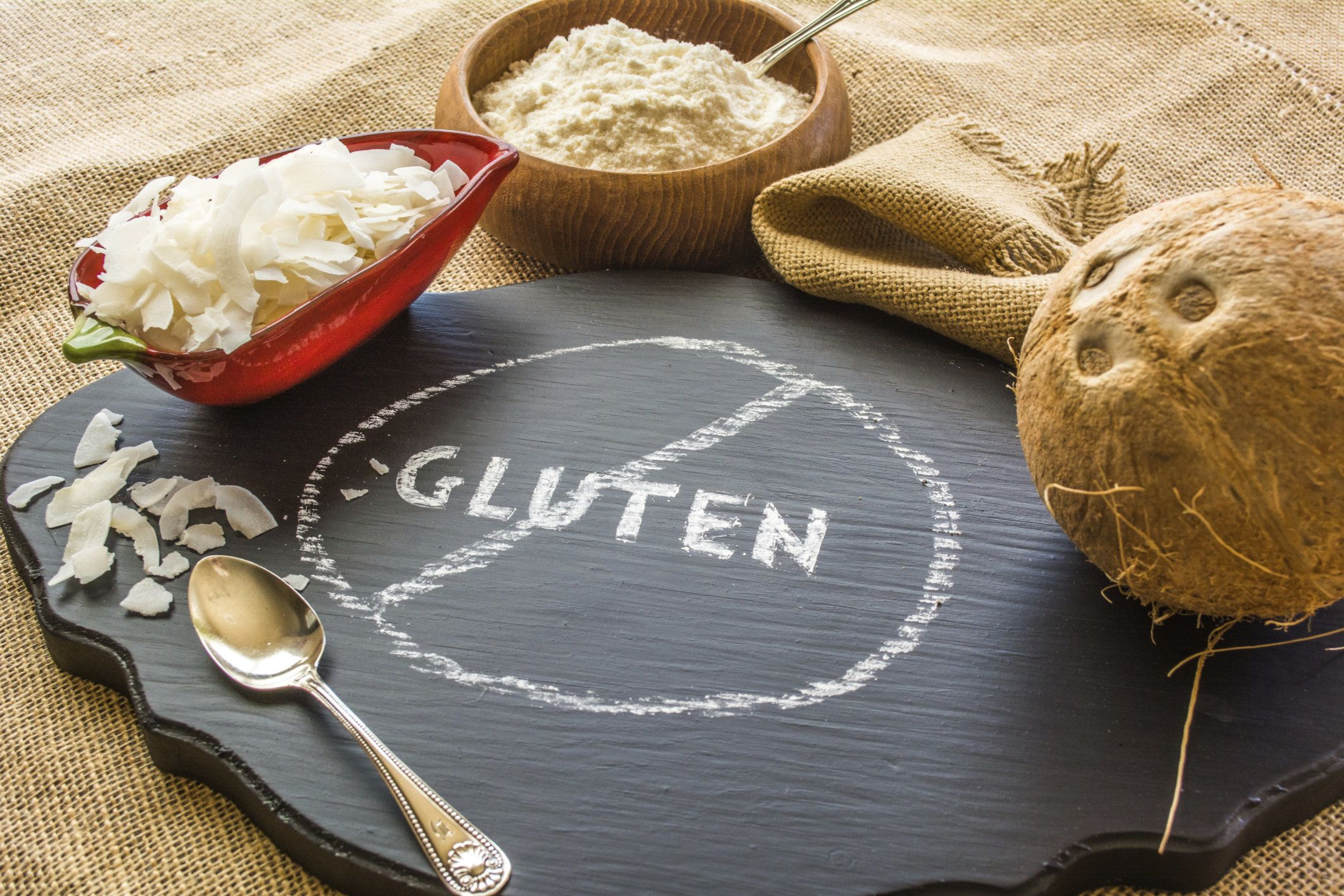 Photo of Coconut, Coconut chips and Coconut flour against a background of burlap with a no gluten chalkboard sign in the front.