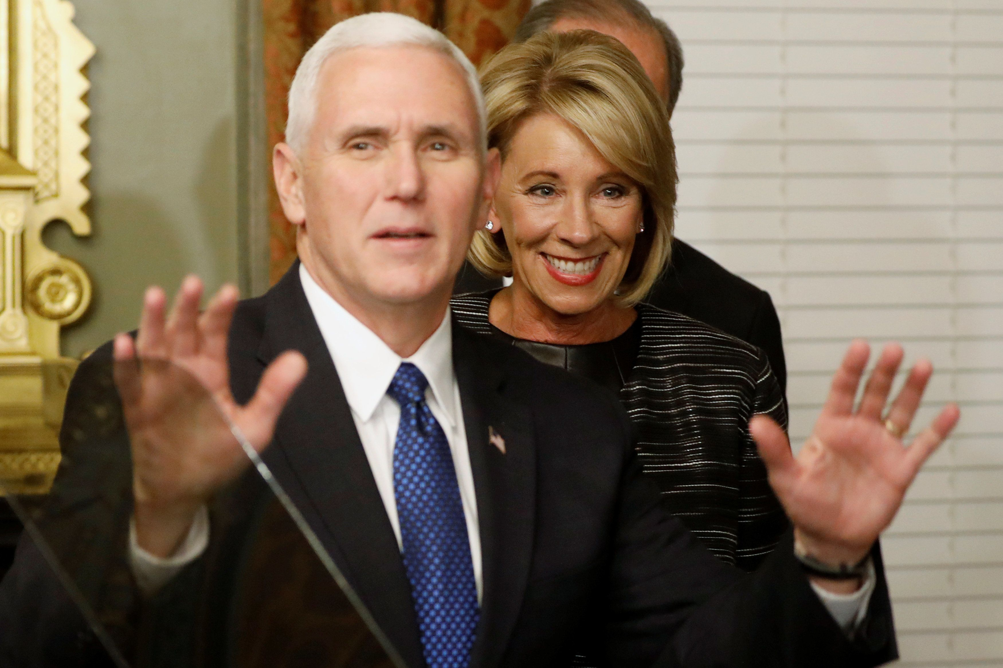 U.S. Vice President Mike Pence (L) dismisses reporters after swearing in Education Secretary Betsy DeVos (C) at the Eisenhower Executive Office Building at the White House in Washington, U.S. February 7, 2017.  REUTERS/Jonathan Ernst