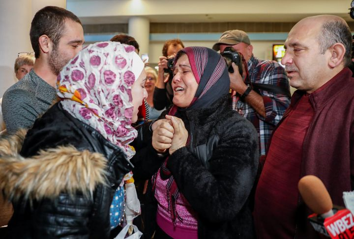 Syrian refugee Baraa Haj Khalaf (L) reacts as her mother Fattoum (C) cries and her father Khaled (R) looks on after arriving