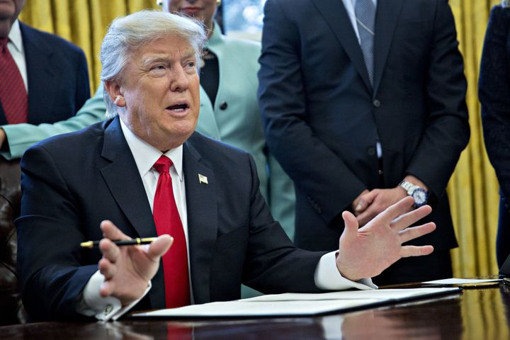 President Donald Trump prepares to sign an executive order that he says will reduce regulations on Jan. 30, 2017.