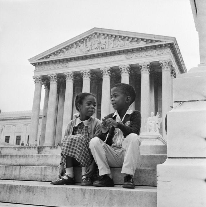 Children sit in front of the Supreme Court, which was hearing arguments about the integration of Little Rock schools.