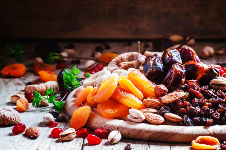A plate of dried apricots, cranberries and dates.