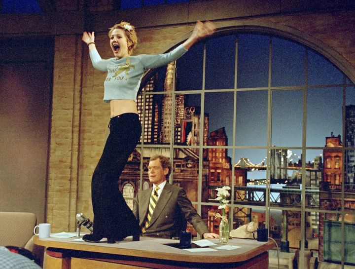 """Drew Barrymore stands atop David Letterman's desk on an infamous 1995 """"Late Show"""" episode."""
