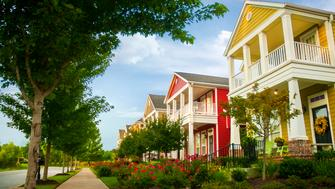 Row of colorful garden homes with two stories and white pillars in suburban neighborhood of Fayetteville, Arkansas