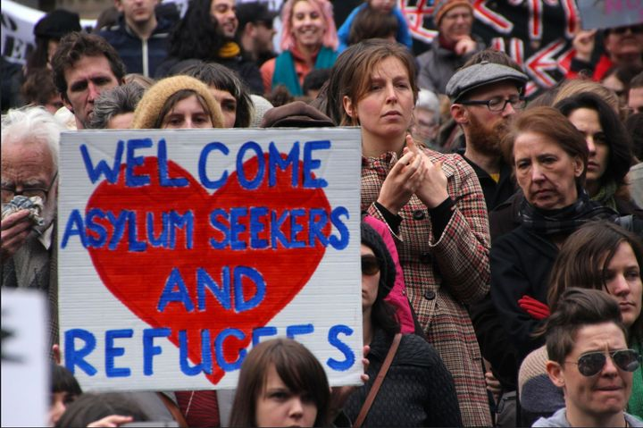 Demonstrators hold signs in support of asylum seekers at a rally supporting refugees.