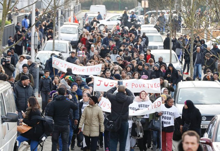 "People hold signs reading ""Justice for Theo"" during a protest on Feb. 6, 2017, in Aulnay-sous-Bois, northern Paris."