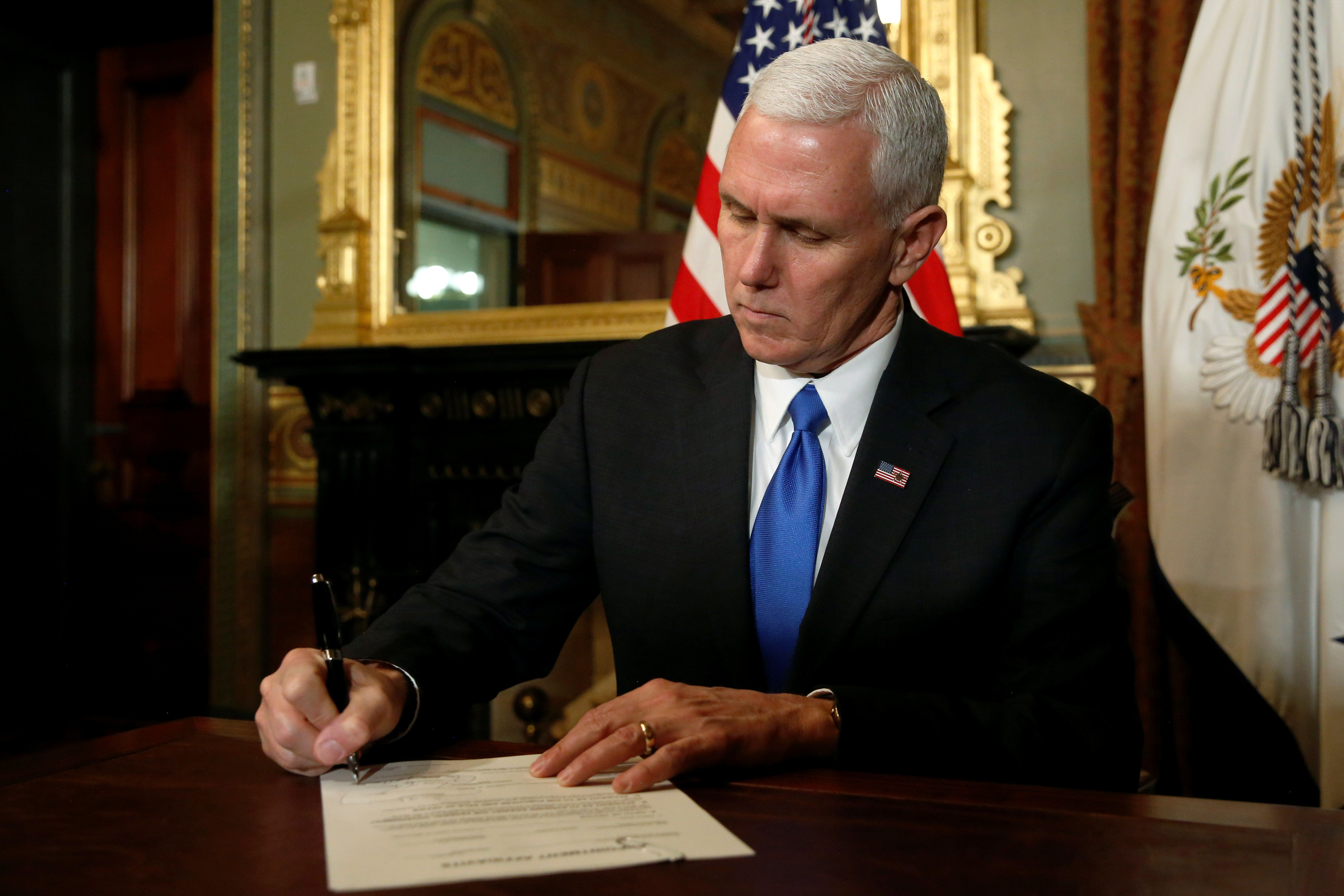 U.S. Vice President Mike Pence signs the document confirming retired U.S. Marine Corps General John Kelly to be Secretary of Homeland Security in his ceremonial office in the Eisenhower Executive Office Building at the White House in Washington, U.S. January 20, 2017. REUTERS/Jonathan Ernst