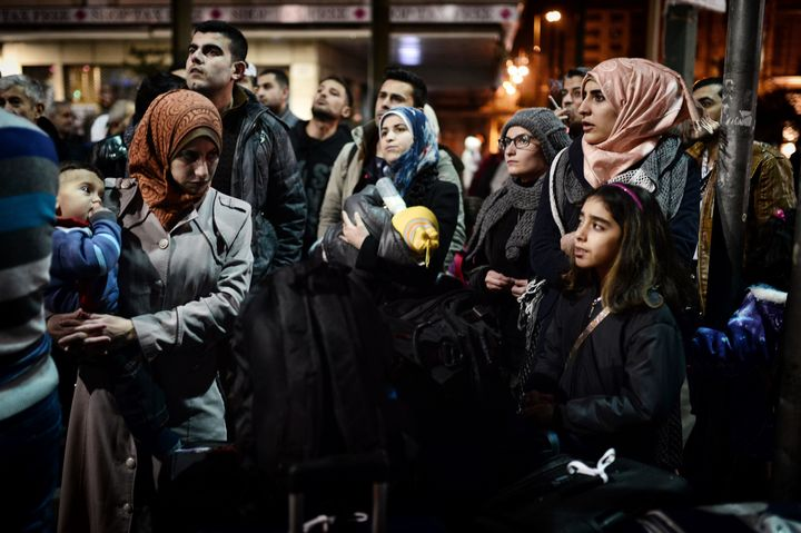 Refugees wait for a bus heading to the airport in Athens to take a special charter flight bound for France. The group consist
