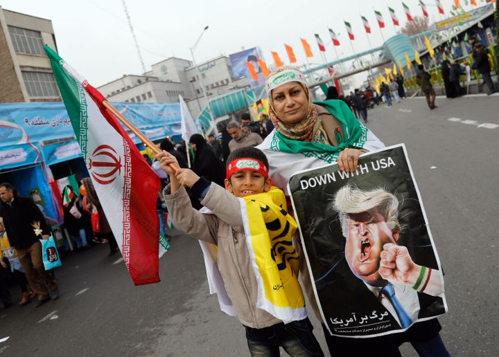 An Iranian woman holds a placard showing a caricature of US President Donald Trump being punched by a hand wearing a bracelet