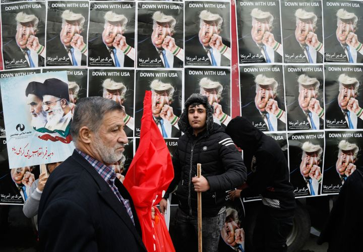 An Iranian man stands in front of placards showing a caricature of President Donald Trump during a rally marking the annivers