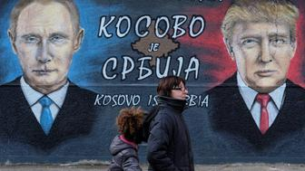 "A woman with a child walks past a mural of U.S. president-elect Donald Trump and Russian President Vladimir Putin in Belgrade, Serbia, December 4, 2016. The text on the mural reads in Russian, Serbia and English ""Kosovo is Serbia"".  REUTERS/Marko Djurica"