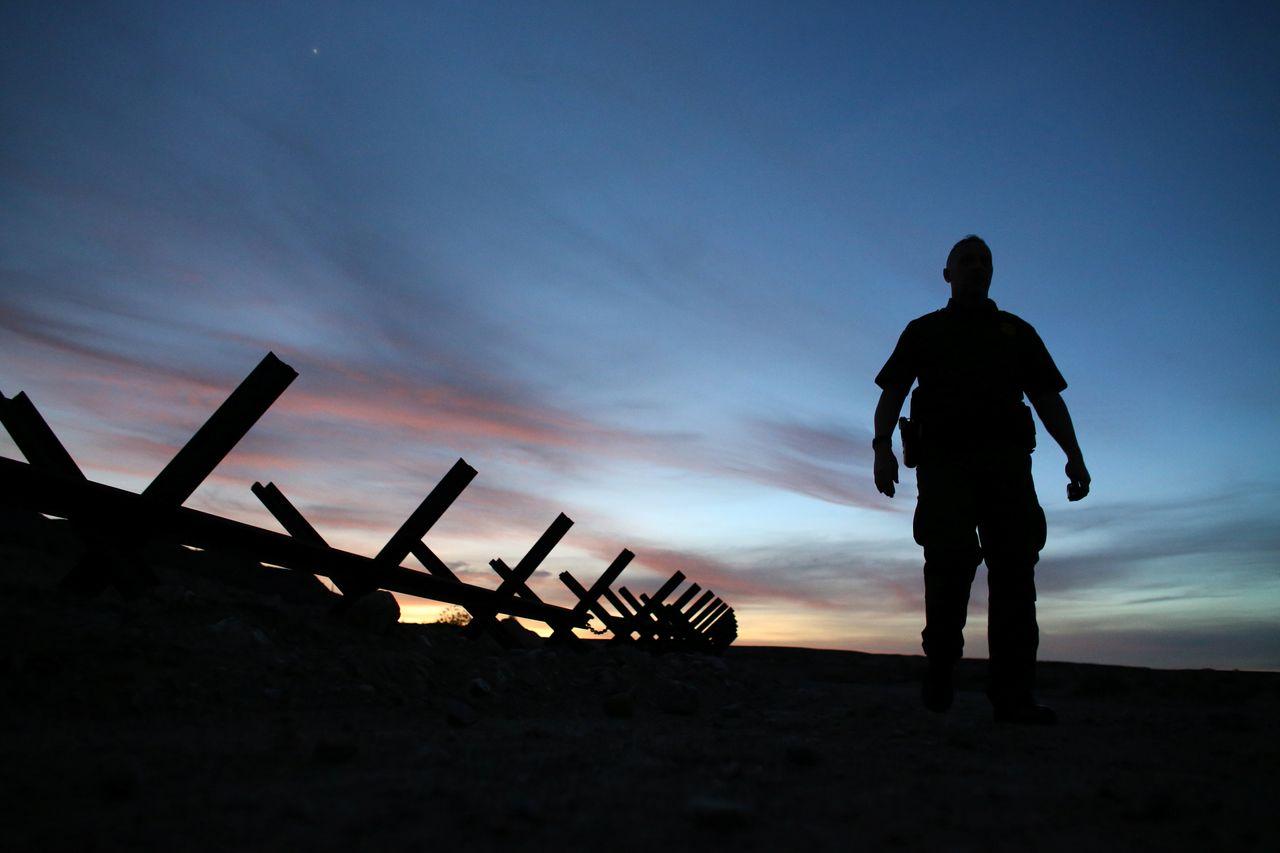 U.S. border patrol agent Alessio Faccin walks along the border fence separating Mexico from the U.S. near Calexico, California. Feb. 8.