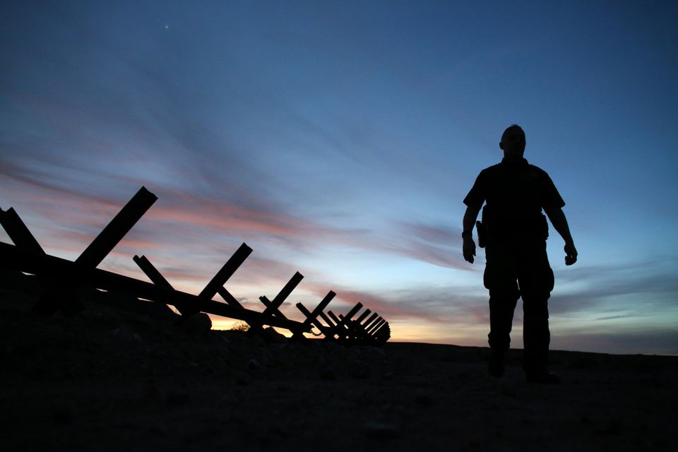 U.S. border patrol agent Alessio Faccin walks along the border fence separating Mexico from the U.S. near...