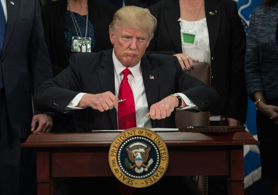 Trump takes the cap off a pen to sign an executive order to start the Mexico border wall project at the Department of Homelan