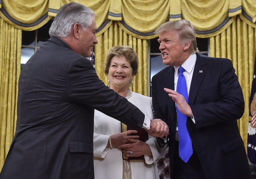 Trump, right, shakes hands with Rex Tillerson, left, as Tillerson's wife, Renda St. Clair, looks on after Tillerson was sworn
