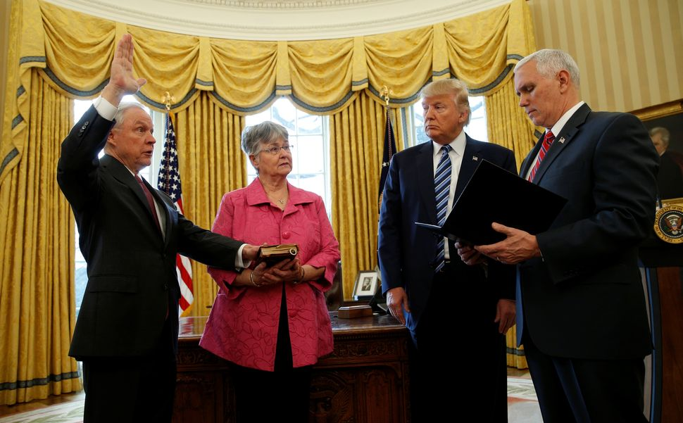 Trump watches as Vice President Mike Pence, right, swears in Jeff Sessions, left, as U.S. attorney general while his wife, Ma
