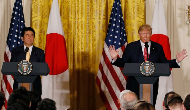 Shinzo Abe looks on as Donald Trump speaks during the press