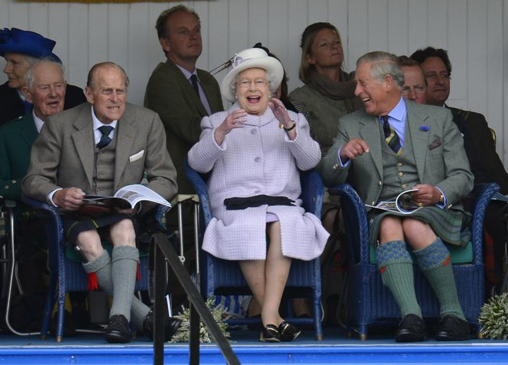 Philip, Elizabeth and their son Prince Charles cheer during the Braemar Gathering highland games in Braemar, Scotland, on Sep