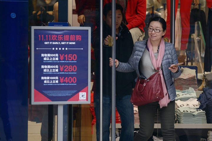 A woman walks out a shop past a 'Singles Day' sales promotional board in Beijing on November 11, 2015.