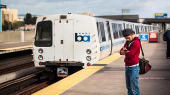 Man in red sweater, hat, and sling bag, with arms folded, looks at his smartphone. A BART train is in the background. Oakland, California. Taken March 24, 2015.