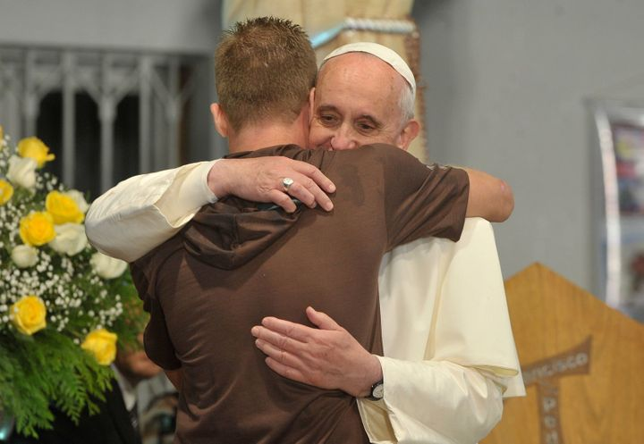 Pope Francis hugs a man in his visit to a rehab hospital.