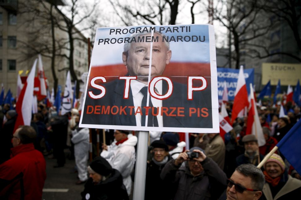 "A man holds a banner with Jaroslaw Kaczyński, leader of Poland's ruling PiS party, that reads ""Stop Demoktaturze (a combinati"