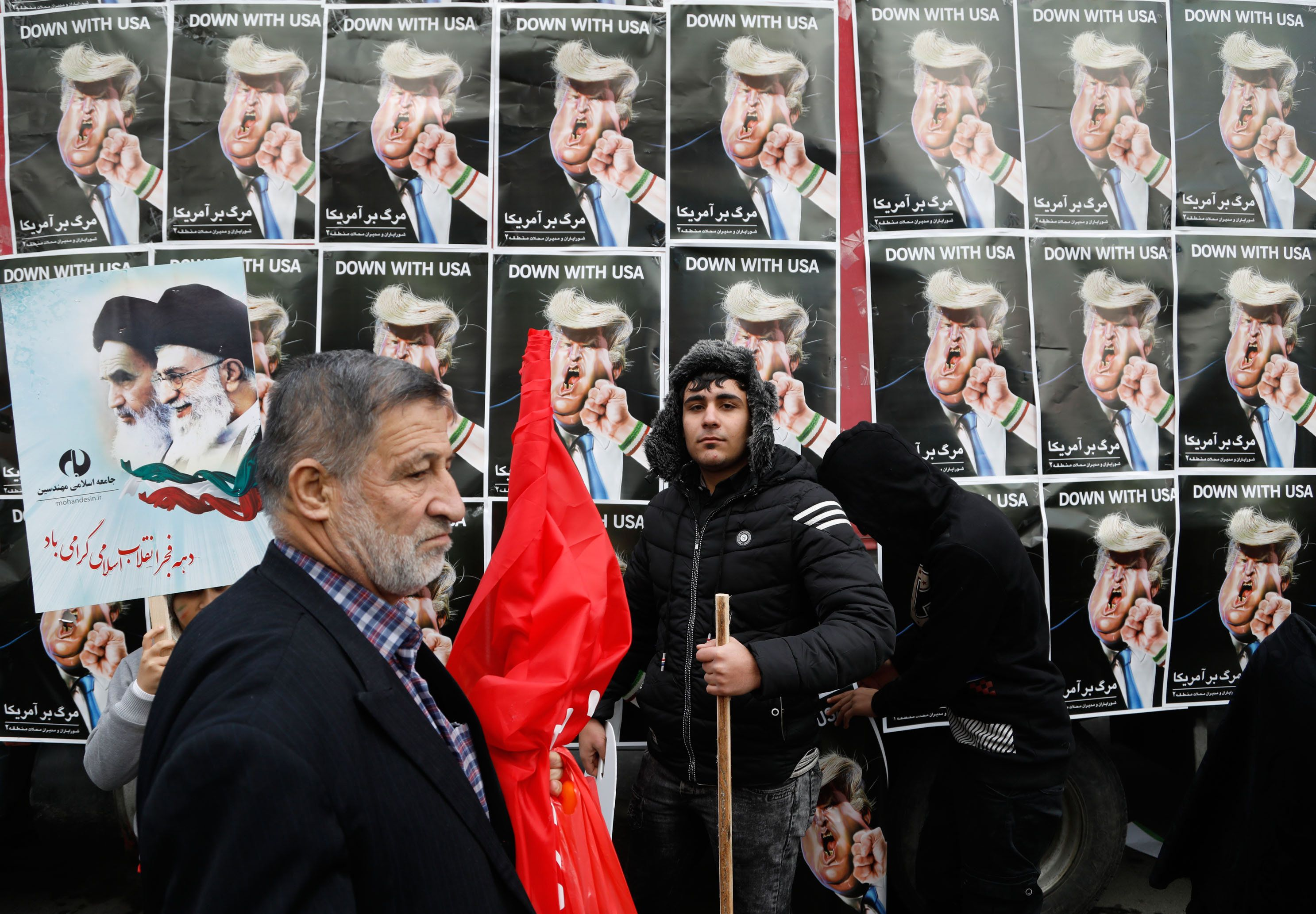 An Iranian man stands in front of placards showing a caricature of US President Donald Trump being punched by a hand wearing a bracelet of the Iranian flag during a rally marking the anniversary of the 1979 Islamic revolution on February 10, 2017, in the capital Tehran. Millions of Iranians marched on the anniversary day in what President Hassan Rouhani described as a response to the new US administration and a rejection of 'threatening language'. / AFP / ATTA KENARE        (Photo credit should read ATTA KENARE/AFP/Getty Images)