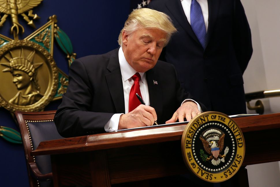 U.S. President Donald Trump signs an executive order to impose tighter vetting of travelers entering the United States, Jan.