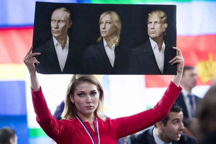 A journalist holds a poster with portraits Vladimir Putin, Marine Le Pen  and Donald Trump, prior to Putin's annual news conf