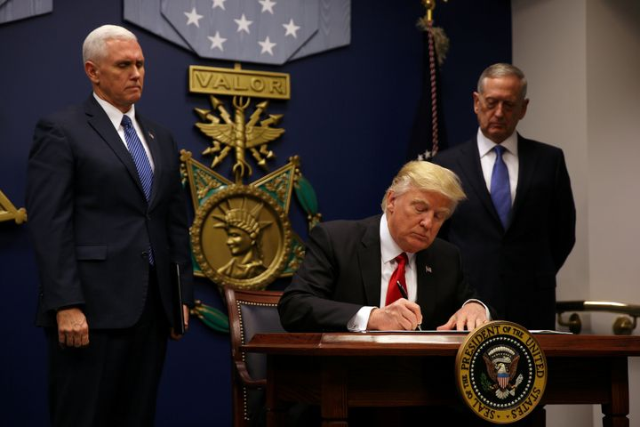 President Donald Trump signs an executive order he said would impose tighter vetting to prevent foreign terrorists from enter