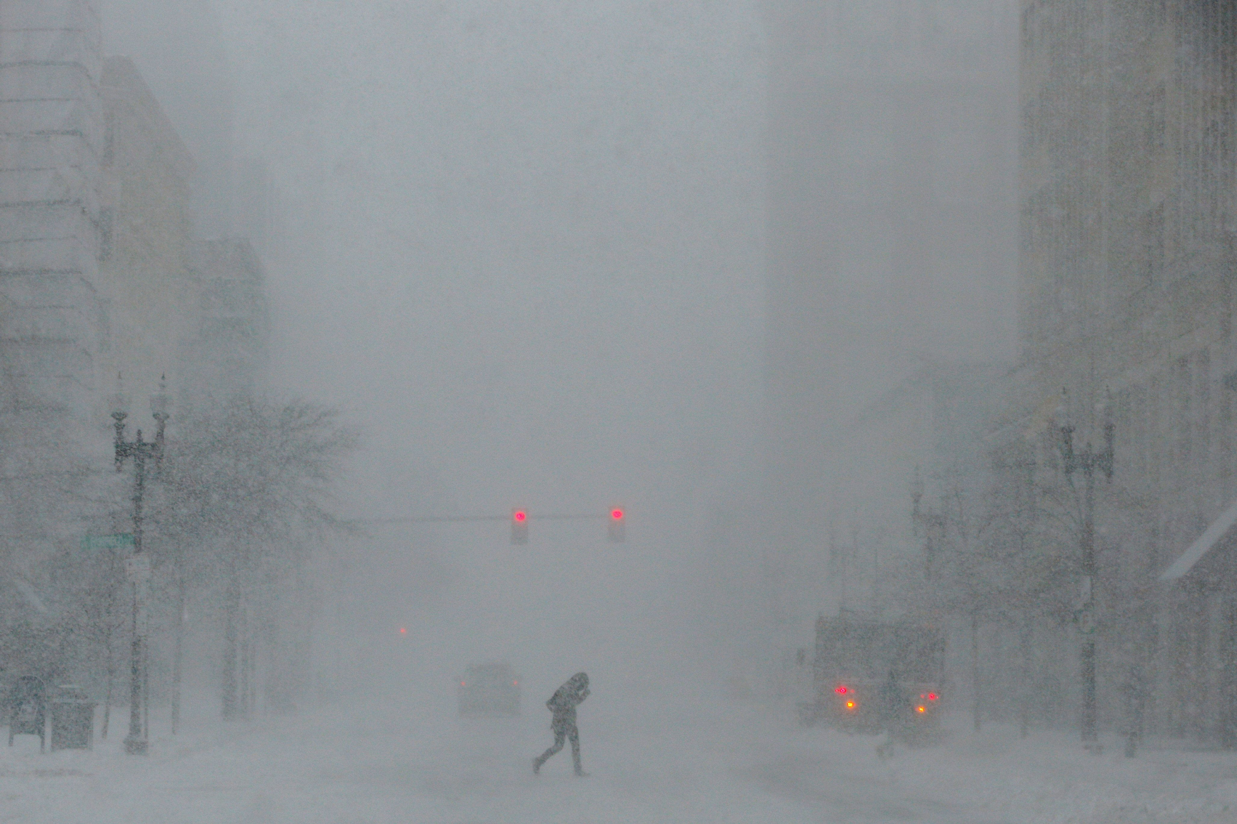 A pedestrian crosses Boylston Street during white-out, blizzard-like conditions in a winter nor'easter snow storm in Boston, Massachusetts, U.S. February 9, 2017.   REUTERS/Brian Snyder