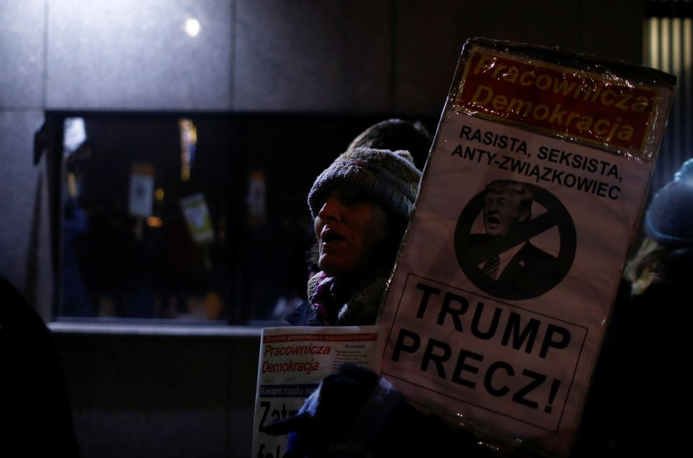 "A woman holds a placard saying ""Trump Away!"" as people gather to protest against U.S. President Donald Trump in front of"