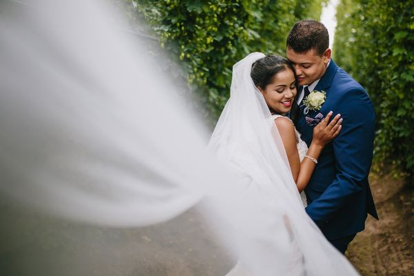 """Jurich and Glenecia braving the rain for intimate wedding portraits in between rows of hops in the Waboomskraal Valley, Sout"