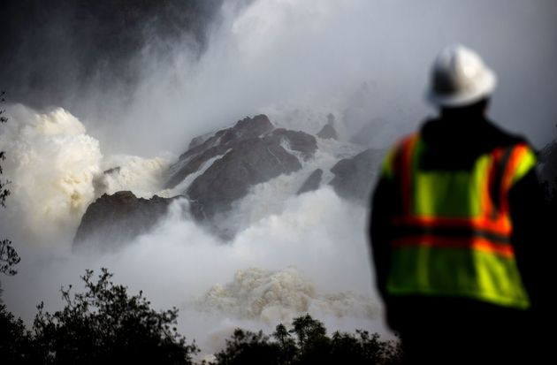 A water utility worker looks on as water is released down a spillway as an emergency measure at...