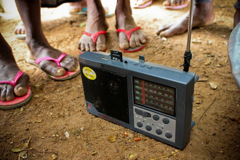 Farmers gather around a radio in northern Ghana