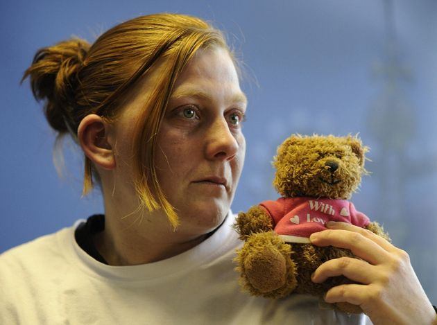 Karen Matthews holding her daughter's favourite teddy bear as she makes an emotional appeal for her safe...