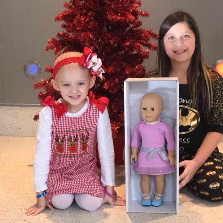 this little girl is giving bald american girl dolls to kids with
