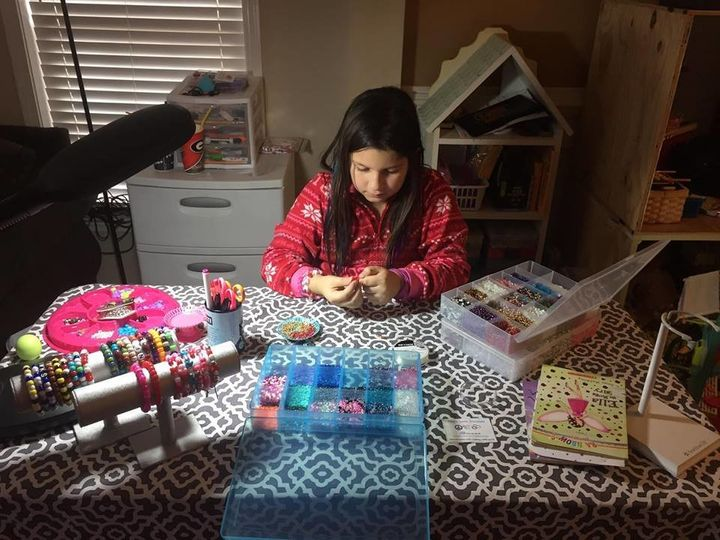 Bella set up shop in her playroom to make bracelets, which she sells to raise money for the dolls.