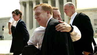WASHINGTON - JUNE 26:  (NO U.S. TABLOID SALES)  Bill Hohengarten (center L) and Paul Smith, attorneys for plaintiffs John Lawrence and Tyron Garner, hug outside the U.S. Supreme Court building June 26, 2003 in Washington, D.C. as Ruth Harlow (L) and Kevin Cathcart (R), Lambda Executive Director, walk by, after the Court struck down sodomy laws that make it a crime for persons of the same sex to engage in sexual relations. This was a major victory for gay rights advocates. Smith argued against the ban before the court earlier in the year, and Harlow was the lead attorney, and legal director at Lambda Legal.  (Photo by David Hume Kennerly/Getty Images)