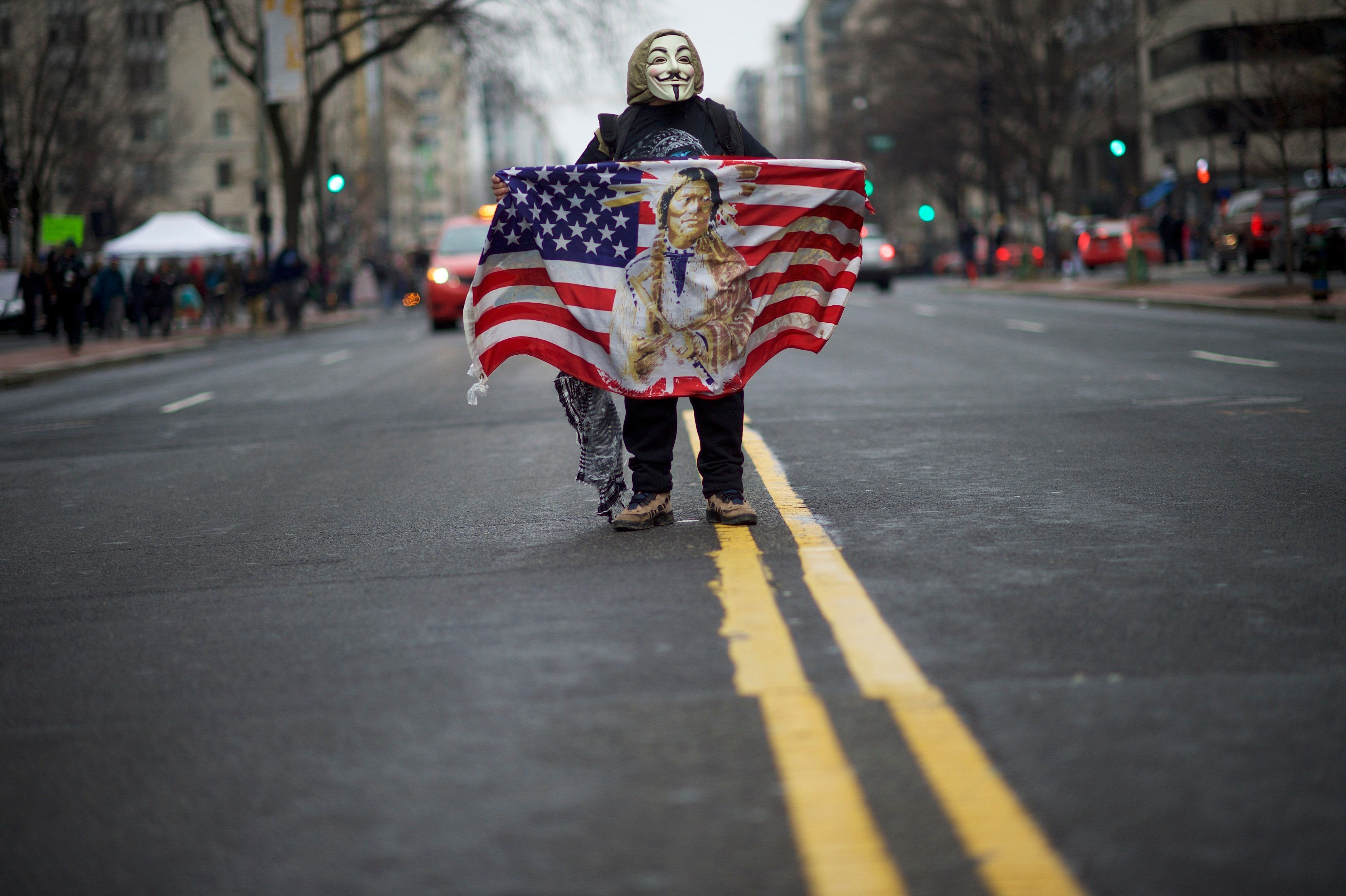 WASHINGTON, DC - JANUARY 20:   A protestor wearing a Guy Fawkes mask demonstrates in the street after the inauguration of Donald Trump as the 45th President of the United States January 20, 2017 in Washington D.C.  Hundreds of thousands of people attended to both celebrate and protest.  (Photo by Mark Makela/Getty Images)