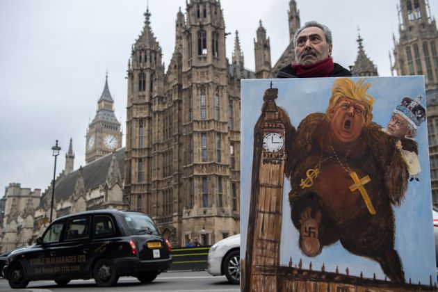 Artist Kaya Mar holds his latest political satire painting of Donald Trump depicted as King Kong with...